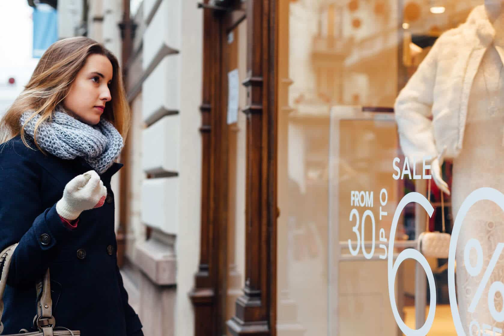 50310631 - elegant woman with scarf and winter gloves looking at boutique showcase