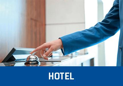 Kassensoftware ErwPerson im Anzug in einem Hotel, vor dem Empfang, drückt auf eine Tischglocke bezugnehmend auf das GastroSoft Hotel Add-On